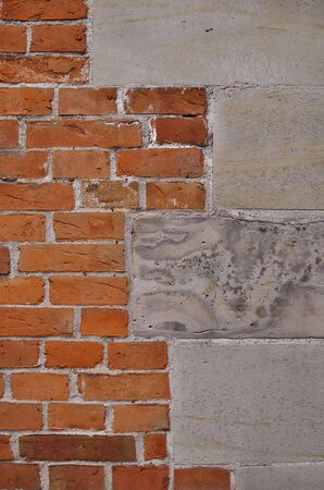 built: Frontal portrait view of a brick wall built attached to a granite wall with irregular meeting points Stock Photo