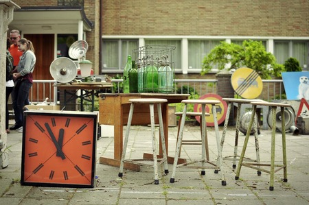 flee: April 2014, Apollolaan, Amsterdam. An orange colored retro wall clock, four bar chairs and some soda bottle showcased at the traditional flee market on Hollands Kings day, the most important national holiday in the Netherlands.