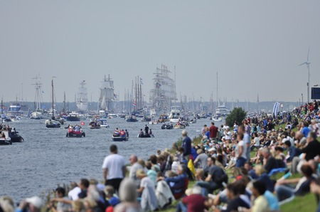19 years: Ij River, Amsterdam, the Netherlands - August 19, 2015: Spectators of looking at the tall ships approaching the port of Amsterdam, at the time of the SAIL 2015 www.sail.nl, an international public nautical event held once in every 5 years since 1975.