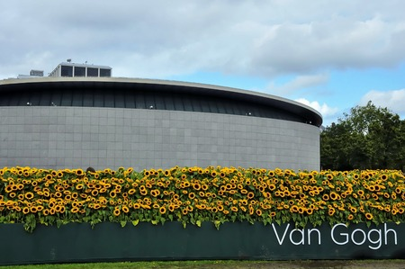 van gogh: Amsterdam, the Netherlands - September 5, 2015: Frontal view of the new reception building of the Van Gogh Museum on the Museum square Museumplein, at the time of the opening ceremony. The organisers used 125,000 sunflowers to build a sunflower labyrinth  Editorial