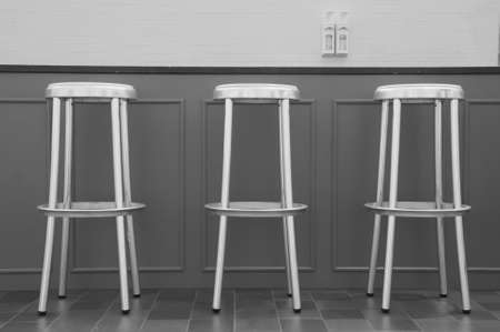 barstool: Three aluminum bar chairs placed in front of a grey bar. Stock Photo