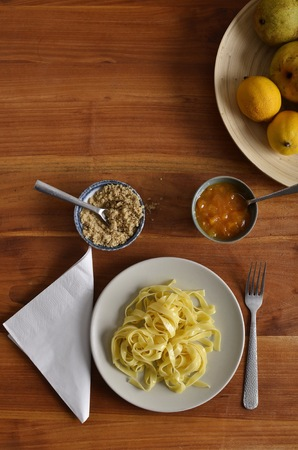 eastern european: Plan view of traditional Eastern European noodles with walnut and jam, on a white plate, accompanied by a plate of fresh fruits.