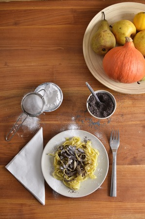 eastern european: Portrait plan view of traditional eastern european poppy seed noodles before mixing, accompanied by a plate of fruits and pumpkin Stock Photo