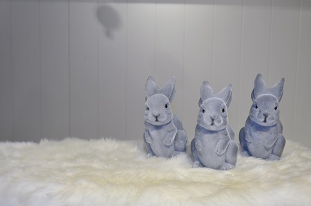 front facing: Facing view of three grey easter bunnies on a white fur surface, in front of a light grey background Stock Photo