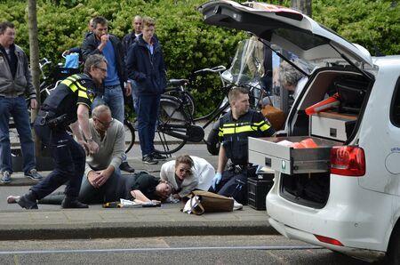 Amsterdam, Nederland - 21 mei 2016: Een gewonde fietser op de grond liggen na te zijn aangereden door een auto, omringd door twee politieagenten en andere pas Byers, naast een open politievoertuig.