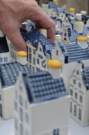 flee: Amsterdam, Netherlands - May 21, 2016: A hand grabbing one of the KLM pottery canal houses at the flee market at the Northern Market (Noordermarkt), in the Jordaan district. Editorial