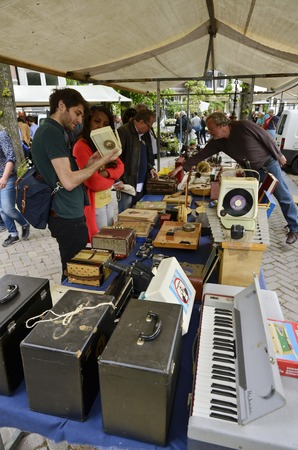 flee: Amsterdam, Netherlands - May 21, 2016: Collectors looking at an item at the weekend flee market at the Nothern Market (Noordermarkt), in the Jordaan district.