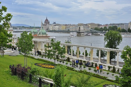 building a chain: Budapest, Hungary - May 15, 2016: The Parliament building and the Szechenyi Chain Bridge viewed from the Castle Garden Bazaar (Varkert Bazar) designed by Miklos Ybl, with pedestrians.