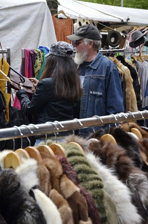 flee: Amsterdam, Netherlands - May 21, 2016: Two visitors looking at the cloths at the flee market on the Northern Market (Noordermarkt), in the Jordaan district.