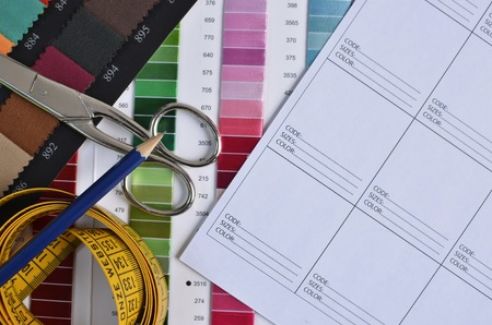 data sheet: Top view of a white design data sheet, a pair of scissors, a pencil on top of a tape measure, fabric and thread samples