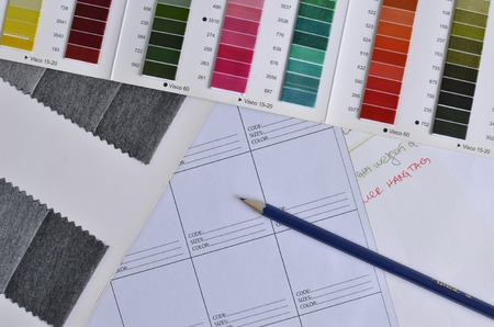 data sheet: Plan view of a pencil, on top of a white data sheet, in the company of thread and grey fabric samples