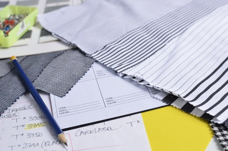 data sheet: Close-up side view of a pencil, on top of a white data sheet, in the company of striped fabric samples and a box of needles