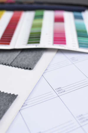 data sheet: Side view of a white data sheet, in the company of thread and grey fabric samples Stock Photo