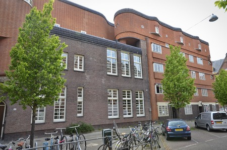 artdeco: Amsterdam, Netherlands - May 21, 2016: Street view of the north wing of a land mark red brick Amsterdam School building in the Spaarndammerbuurt. Editorial