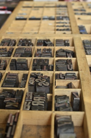 Side view of metallic letters in a wooden grid box, used for letterpress printing on a manual print machine