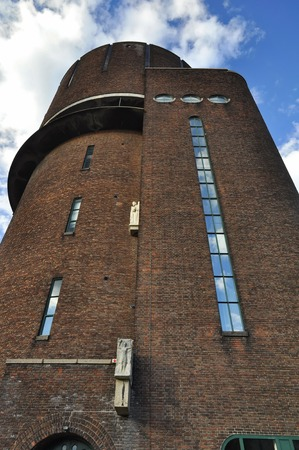 breda: Breda, Netherlands - October 16, 2016: Close-up view of the Amsterdam School style water tower building on the Speelhuislaan, under the cloudy sky