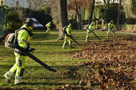 Brussels, Belgium - November 29, 2016: Side view of professionals in fluorescent suits with leaf blowers working in the Cinquantenaire park.