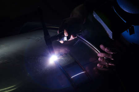 prefabricate: Stainless steel welder in small factory with lens flare style