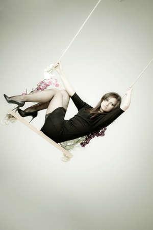 Beautiful girl swinging in studio  Stock fotó
