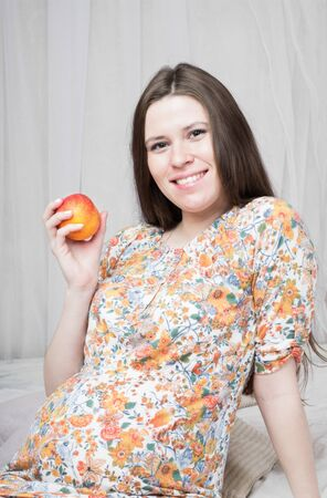 Beautiful pregnant woman holding the peach  Stock Photo