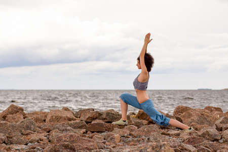 Young woman doing yoga exrecises outdoors