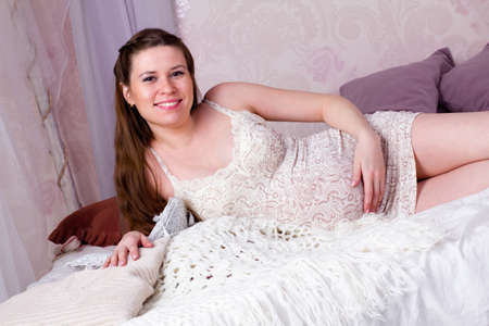 Pregnant woman lying in bed and smiling Stock Photo
