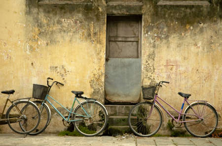 old door: Parked bikes at at street of Hoi An Stock Photo