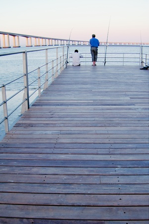 brige: Pescador en muelle cerca de cnetro de Vasco da Gama en Lisboa