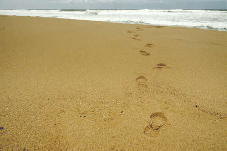 Footsteps at beach on a stormy day Stock Photo