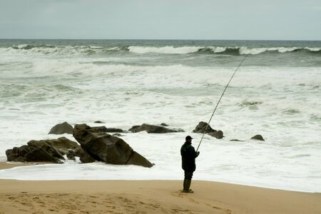 Man fising nearby stormy beacj