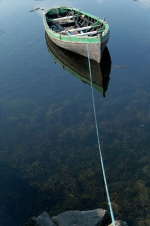 row boat: Small rowboat on a lake tied to the shore Stock Photo