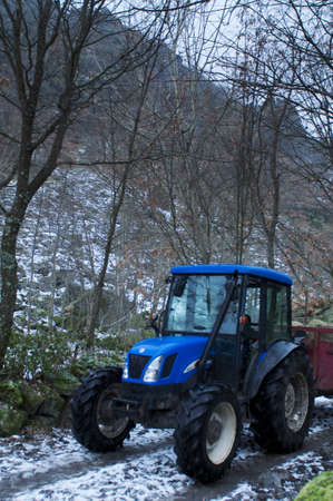 fenceline: Blue tractor with trailer at forest road with snow