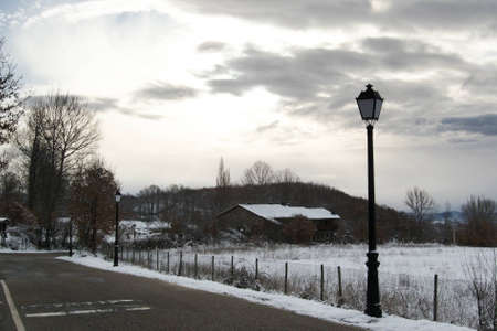 fenceline: Public lamp by sunrise at countryside covered with snow