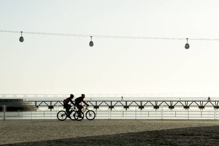 Two bikers passing at Lisbon Parque das Nacoes