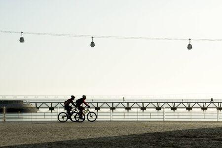 Two bikers passing at Lisbon Parque das Nacoes