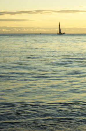 Small sail boat at cruising by sunset