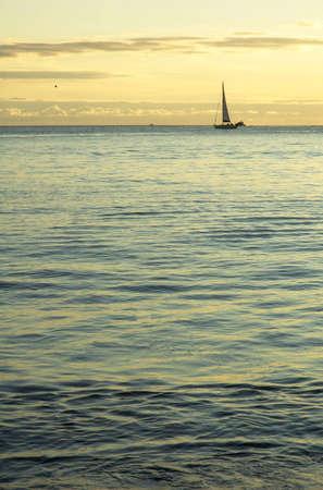 Small sail boat at cruising by sunset