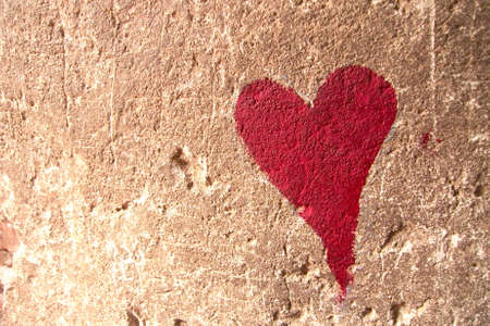 Red heart drawn over brown textured wall