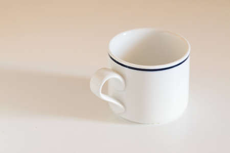 White tea cup with blue rim on white table