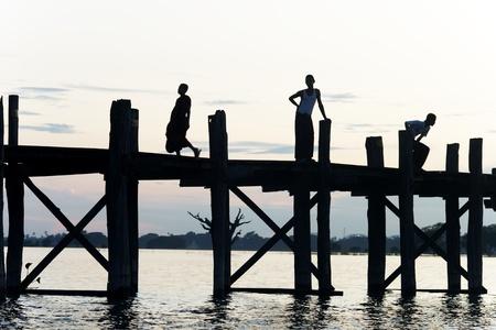 Burmese people at sunset at U Bein bridge Stock Photo