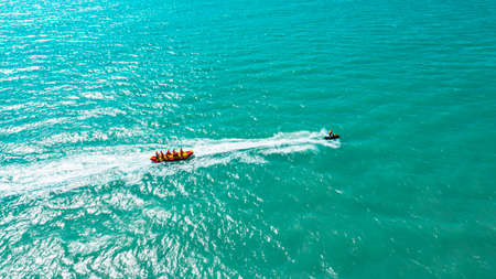 a group of people having a rest together ride an inflatable rubber banana tied to a boat Standard-Bild