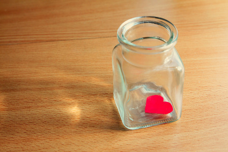 are trapped: Heart trapped in a jar on wooden surface
