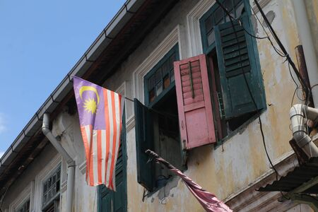 Malaysian flag flying from an old heritage building window 版權商用圖片