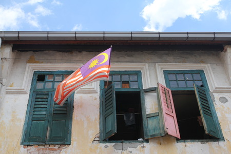 national: Malaysian flag flying from an old heritage building window Stock Photo