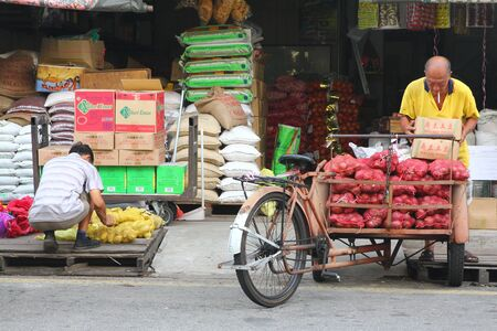 locals: Locals going about their business from an old store in Melaka, Malaysia. Editorial