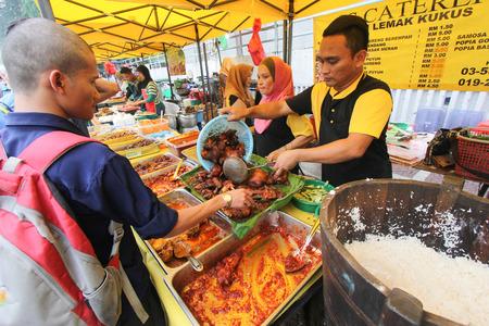 A nasi lemak hawker tends his stall in a ramadhan bazaar