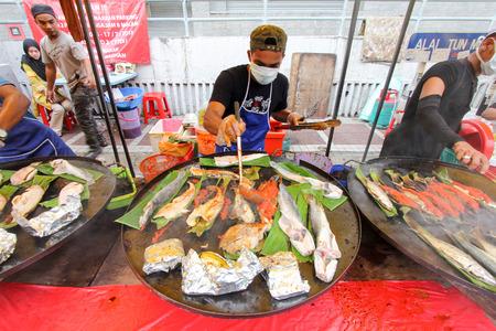 ramadhan 바자에서 구운 생선을 준비하는 마구간 노동자 에디토리얼