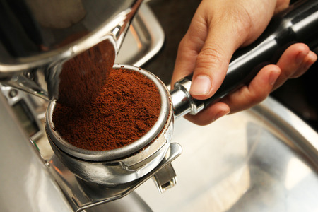 grinded: Freshly grinded coffee being emptied onto coffee holder