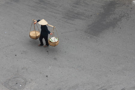 conical: Street vendor with conical straw hat on the streets of Hanoi, Vietnam
