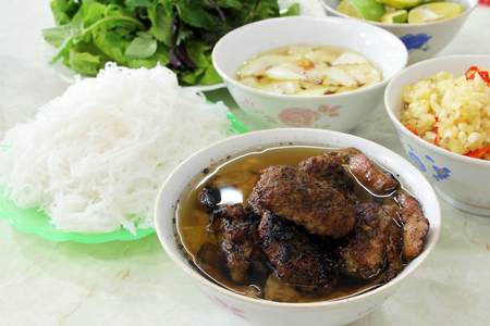 sauce dish: Bun cha, a Vietnamese dish of grilled pork and rice noodles served with fresh herbs and dipping sauce.